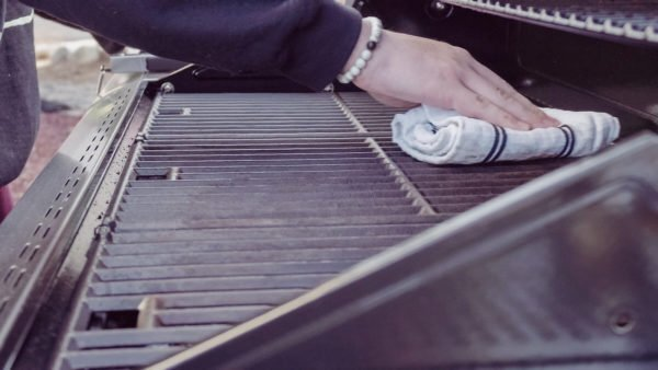 A man cleans a gas grill before storing it