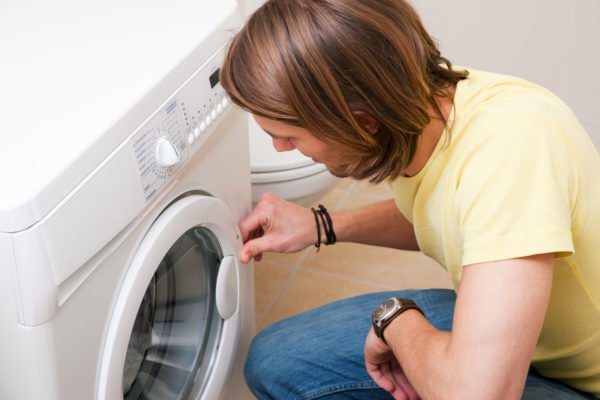 A man opening a washer or dryer