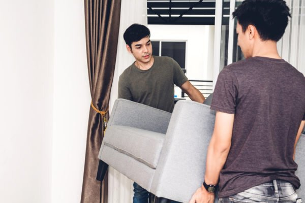 Two boys moving a couch in a home