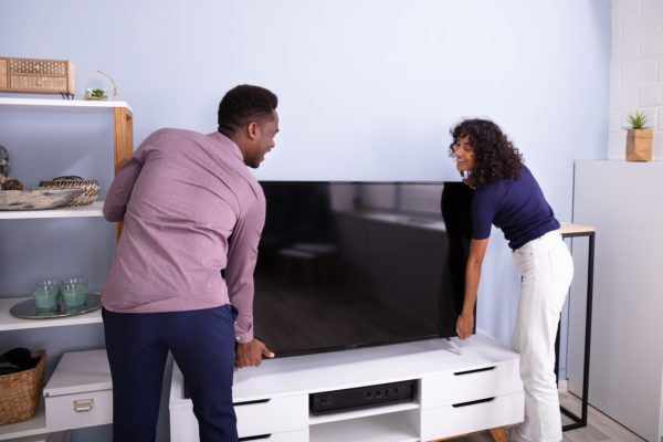 Two people lifting a TV in a room