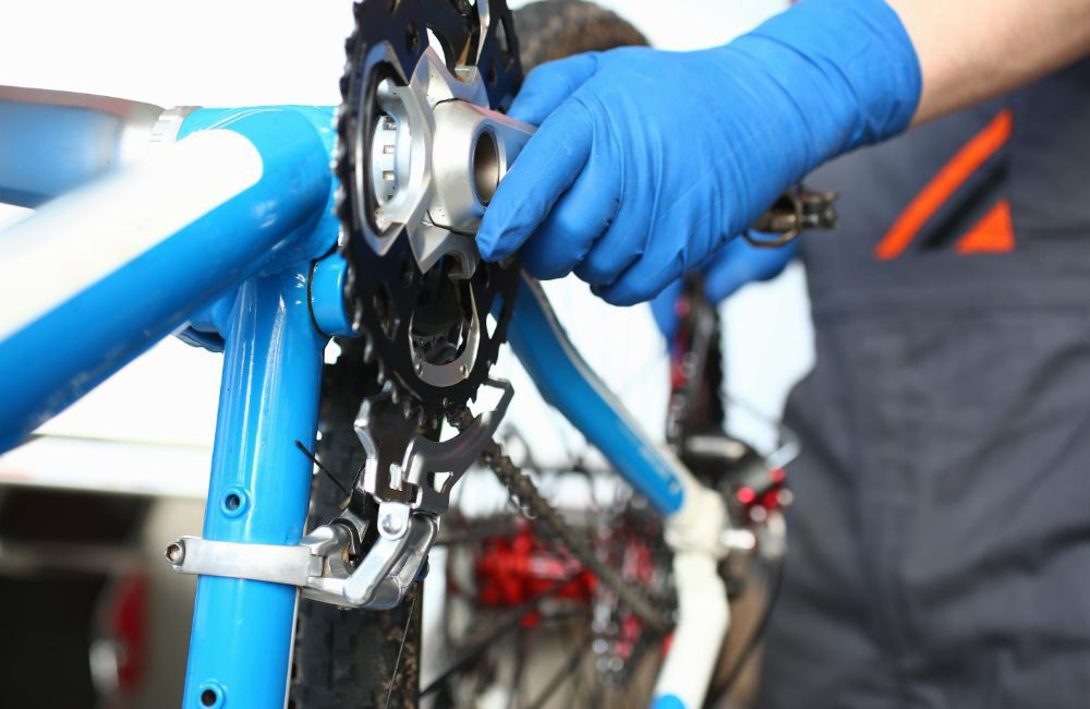 A man tuning up his bicycle after winter storage.
