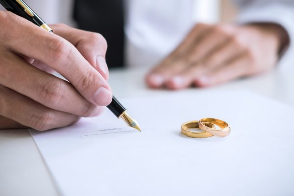 A man signing divorce papers
