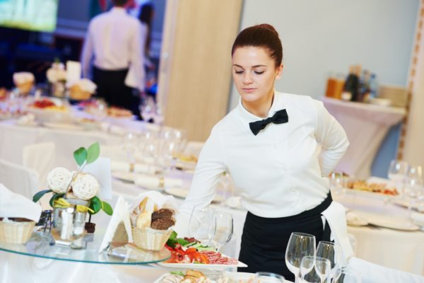 A restaurant worker with catering supplies