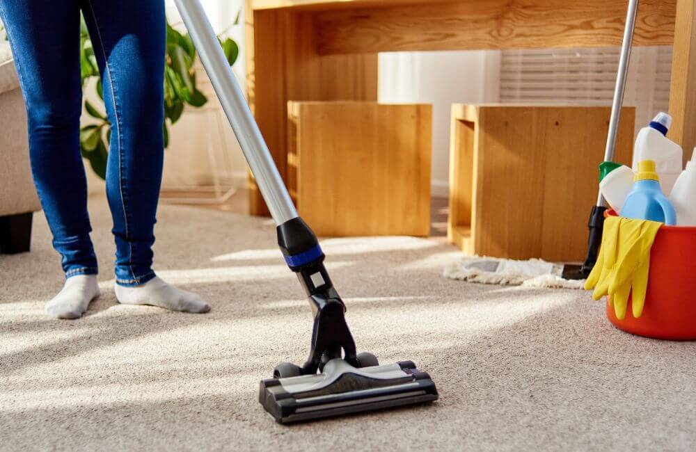 A person vacuuming their home