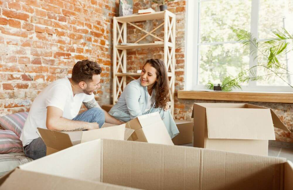 A young couple unpacking boxes in their new shared home