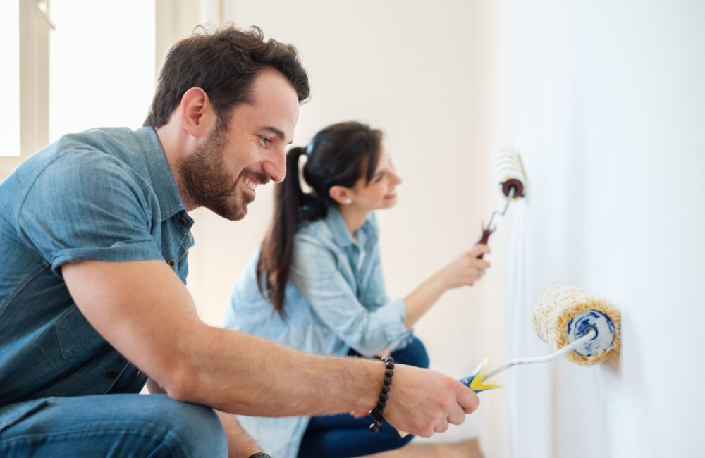 A man and woman happily painting a room to add value to their home.