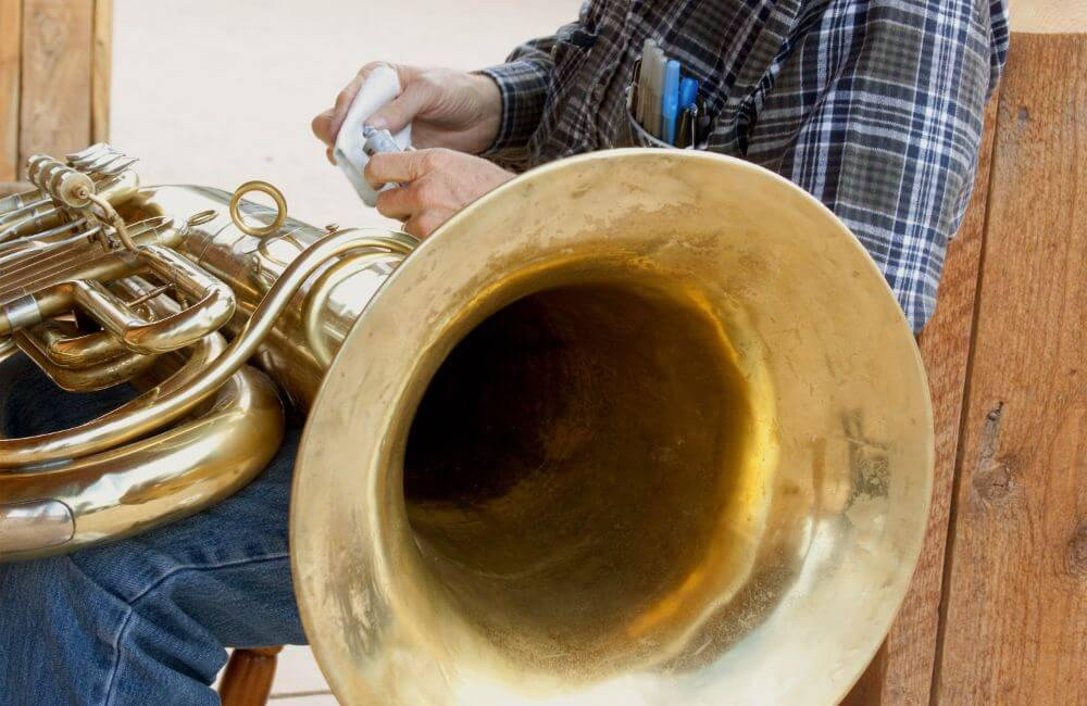 A man cleaning his tuba before putting it in storage.
