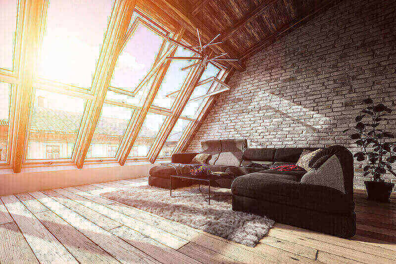 A spacious attic turned into a living room with a large couch and panoramic windows.