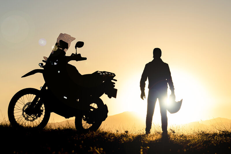 A man stands next to his motorcycle while enjoying the sunset over the mountains.