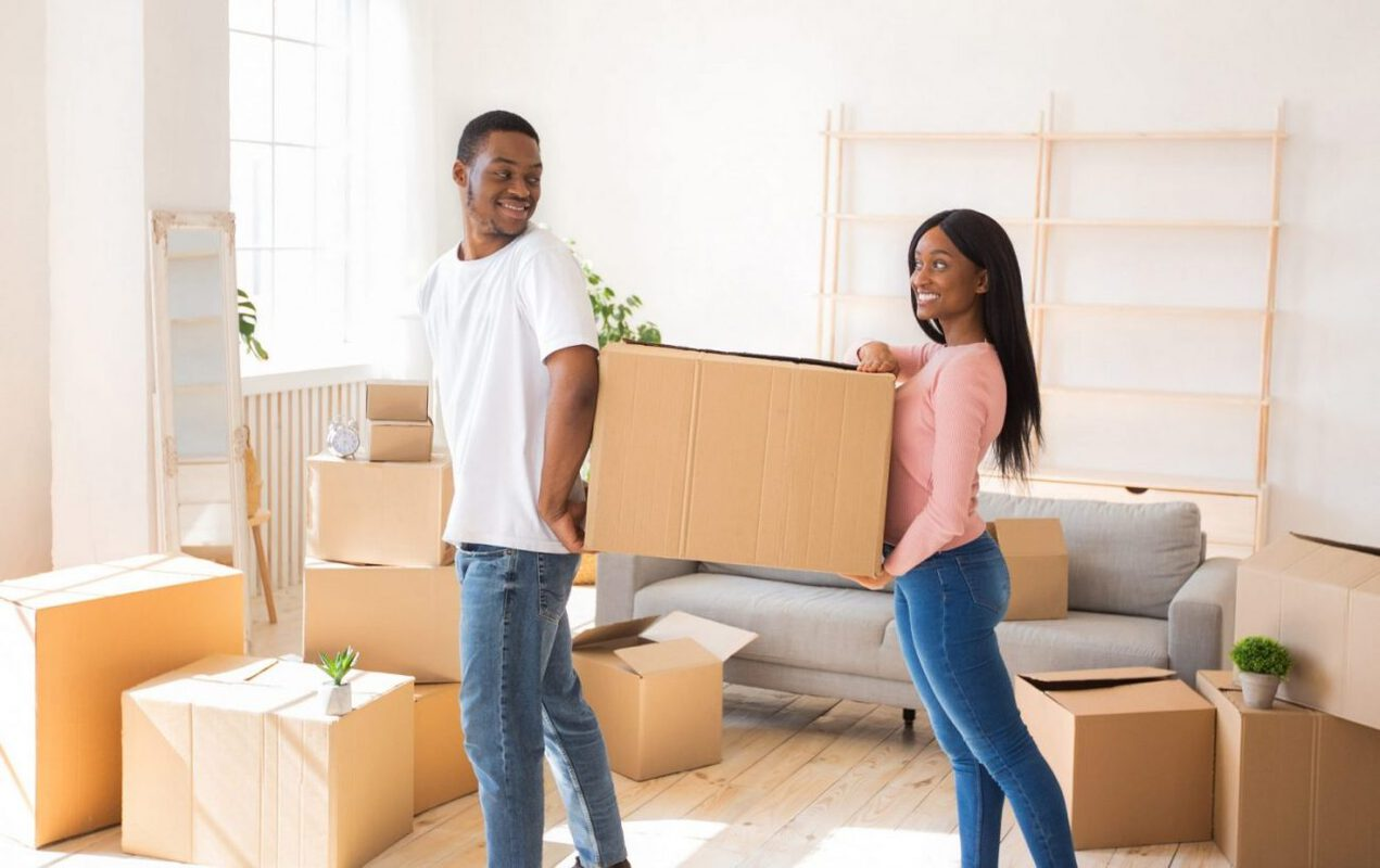 A young couple moves boxes out of their old house to put into their storage unit.