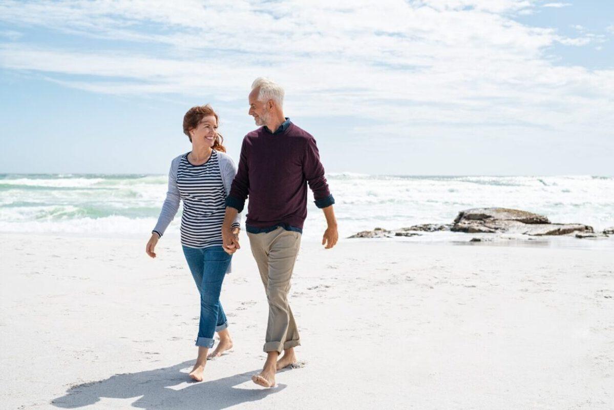 A senior couple walk on the beach for their retirement plan.
