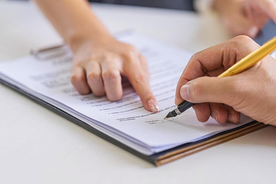 A person signs storage insurance paperwork for their new unit.