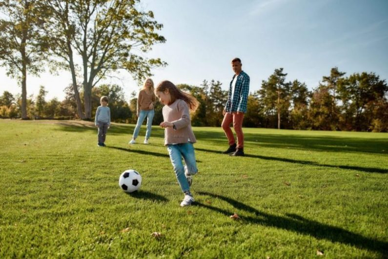 A family plays soccer outside in the summer.