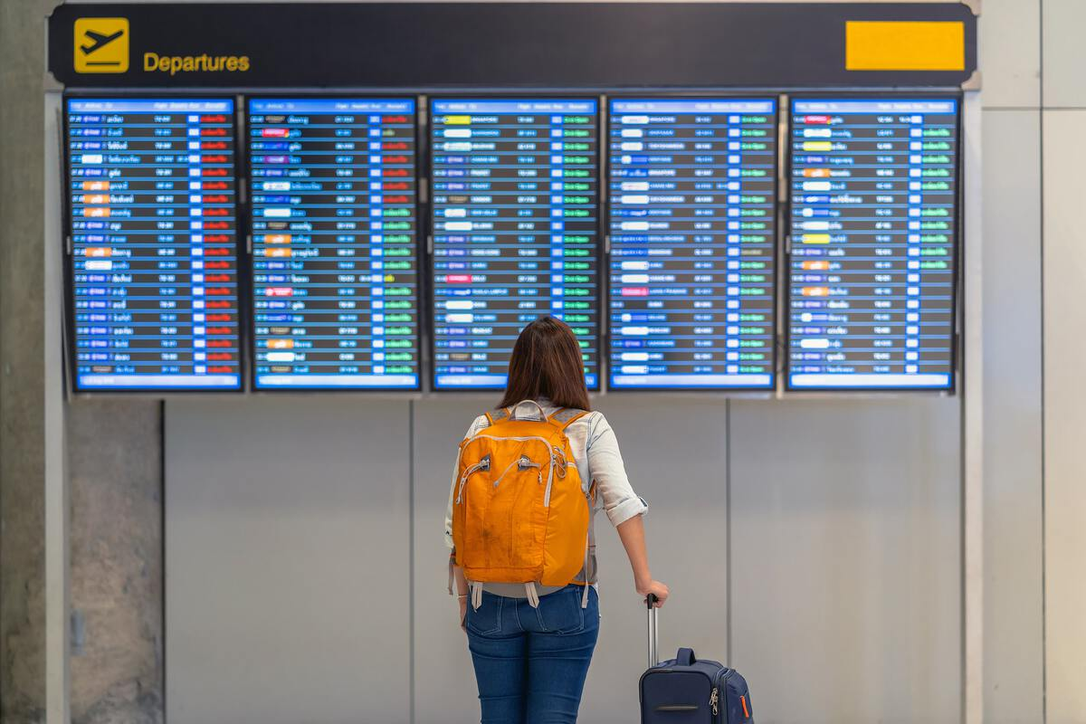 A young woman stands in front of the airport flight schedule.