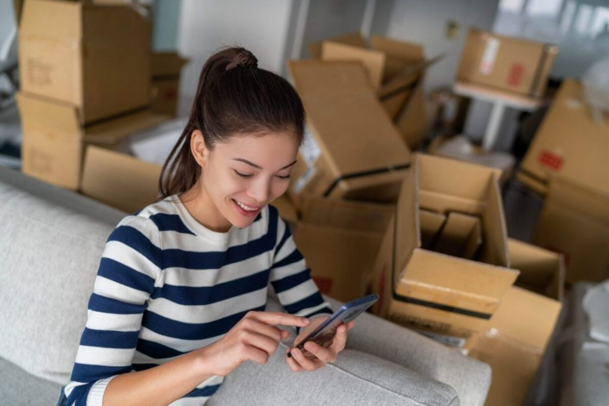 A young woman using a moving app while packing.
