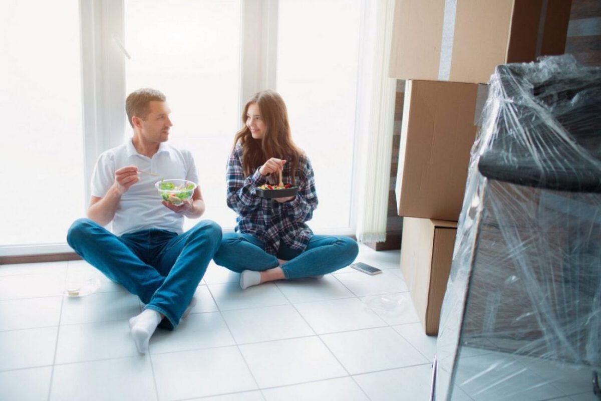 A couple eats dinner while packing for a move.