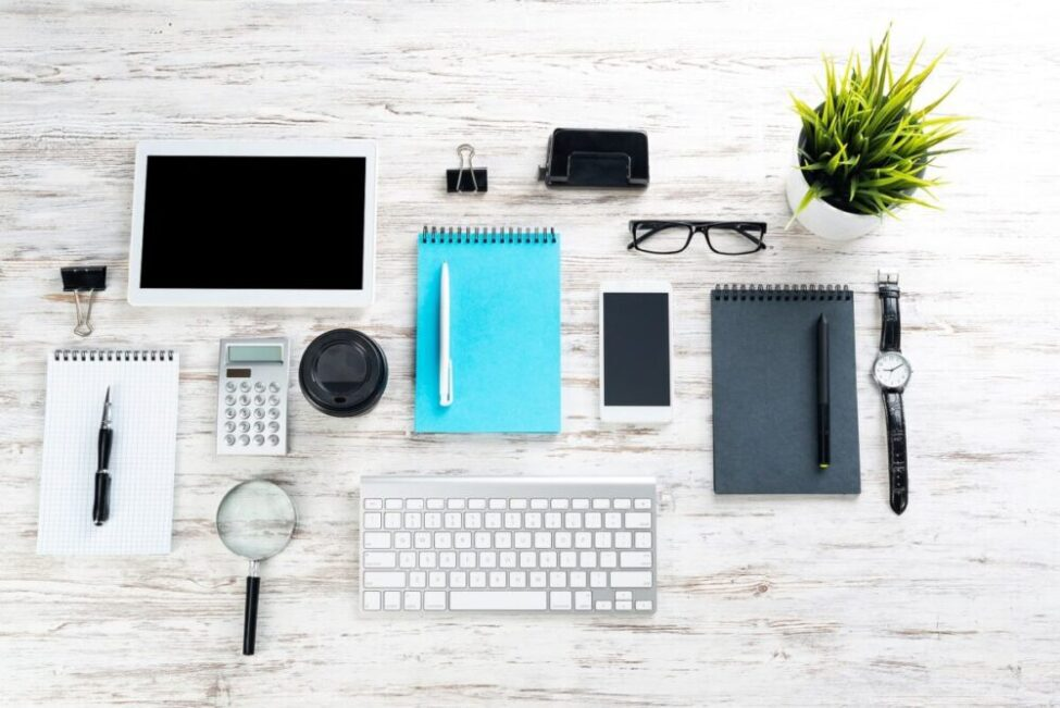 A neatly organized desk of items including a keyboard, notepad, and tablet.